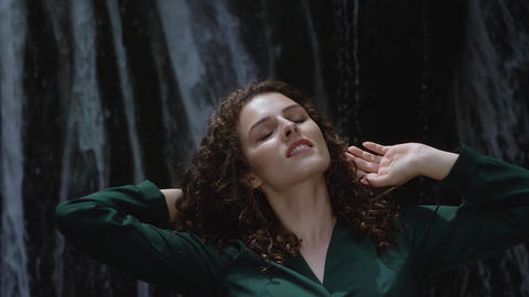 sexy young woman with curly hair shakes them against a waterfall background Footage