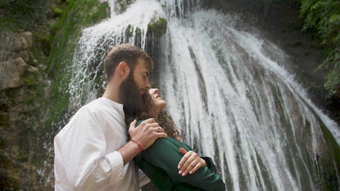 a man with a beard embraces a woman with curly hair behind her who leaned on his Footage
