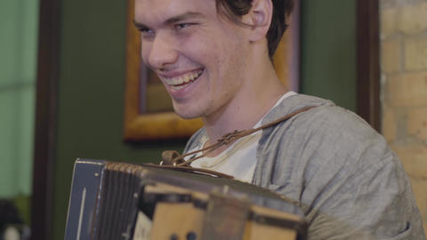 Skill young man playing the accordion smiling. Cheerful music on the old Footage