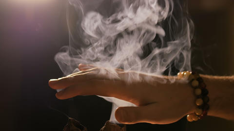 Smoke from incense rises through fingers Live Action