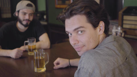 Two men sitting in the bar drinking beer together. Guys having fun together Live Action