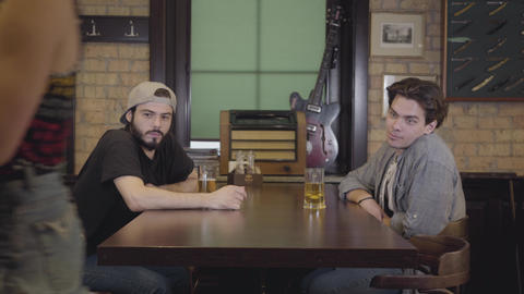 Two men sitting in the bar drinking beer together. Guys having fun together Footage