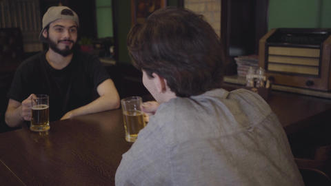 Two guys drink beer while sitting at a table in a pub. Guys having fun together Live Action