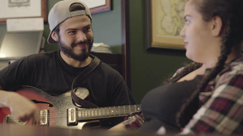 Young smiling bearded man playing guitar in the bar, attractive plump woman Footage