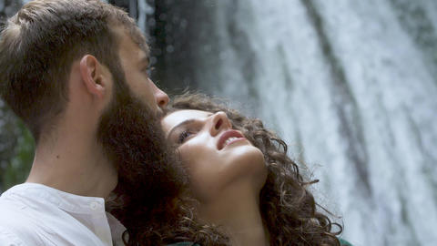 attractive man with a beard hugging a woman with curly hair from behind against Footage
