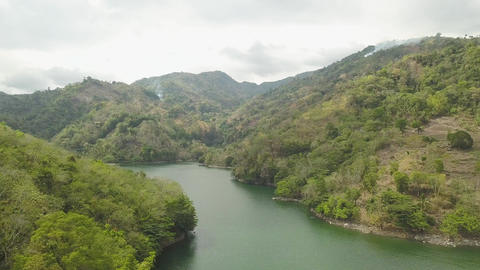 Tropical lake and green highlands landscape from flying drone. Aerial landscape Footage