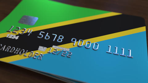 Plastic bank card featuring flag of Tanzania. Tanzanian national banking system Live Action