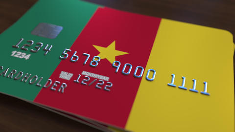Plastic bank card featuring flag of Cameroon. Cameroonian national banking Live Action