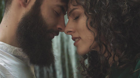 a man and a woman with their eyes closed bowed head to head against the backdrop Footage