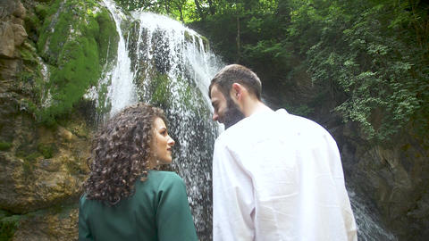 a man with a beard and a woman with curly hair kiss against the backdrop of a Footage