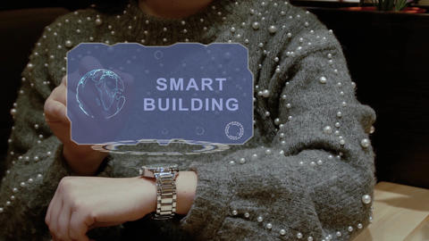Woman uses hologram watch with text Smart building Live Action