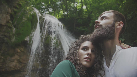 a pair of lovers on the background of a waterfall Footage