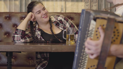 Unrecognizable man playing the accordion while attractive plump woman drinking Footage