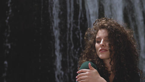 sexy woman with curly hair hugs herself against a waterfall Footage
