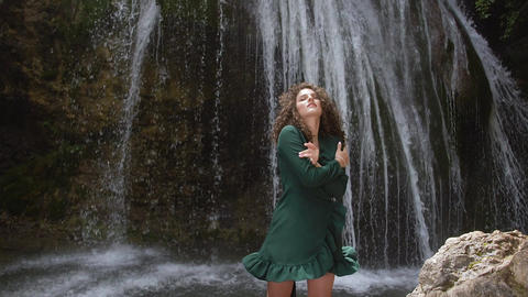 sexy woman with curly hair hugs herself and enjoys the backdrop of a waterfall Footage