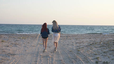 two young women go to the sea along the sandy shore back view slow motion Footage