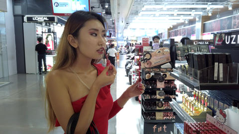 JSP-0628 Young asian woman red dress with shopping at makeup counter Live Action