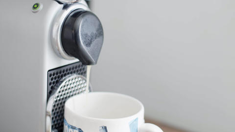 Hot coffee is poured from compact coffee machine spout in cup in kitchen Live Action