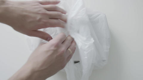 Man's hands put white plastic bag with white paper box in it on white table Live Action
