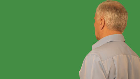 Senior man swiping by finger virtual screen on transparent green background Footage