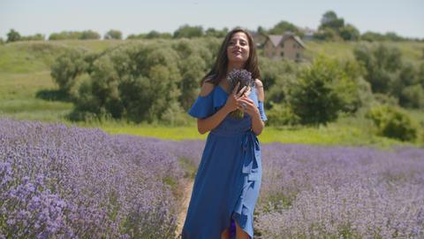 Female smelling fresh fragrant lavender blossoms Live Action