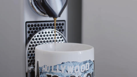 Pouring coffee stream from coffee machine spout in cup with HOLLYWOOD print Live Action