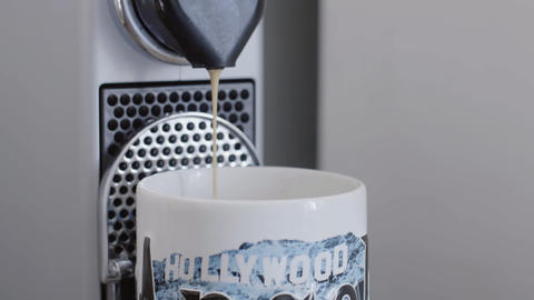 Hot coffee is poured from coffee machine spout in cup with HOLLYWOOD print Live Action