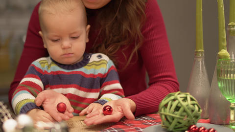 Cute young mother and a baby have fun in modern kitchen. Mom playing with child Footage
