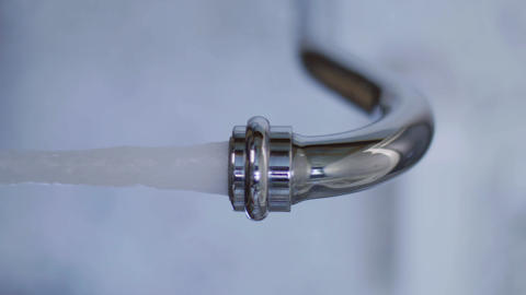 Closeup of tap water starts flowing from tap in when someone turned it on Live Action