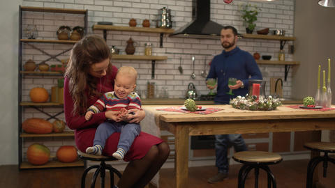 Young pretty woman sitting at the table in the kitchen with baby on her pals Footage