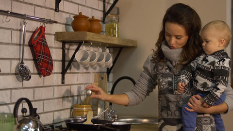 Pretty young woman with a baby in her arms in modern kitchen preparing breakfast Footage