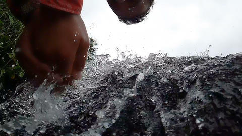 Young man washing his face in a mountain waterfall in Mountains in slo-mo Live Action