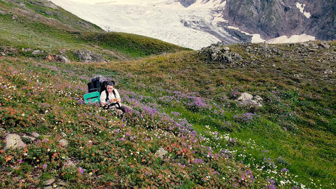 Female mountaineer sitting and smiling among flowers on a mountain in slo-mo Live Action