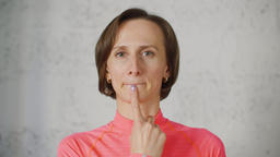 Portrait of woman with finger on her chin under the lips meaning T-letter Footage