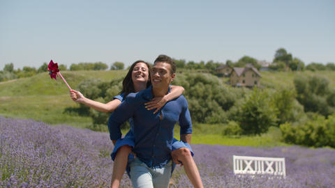 Positive man piggybacking lovely woman outdoors Footage