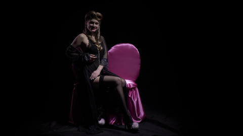 Sexy pin up model on a pink couch is posing on dark background, 4k Acción en vivo