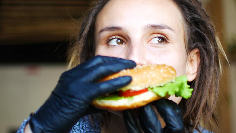 Young caucasian hipster girl is eating a juicy veggie burger and dancing Footage