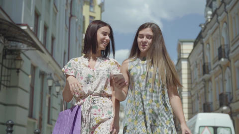 Two cheerful women with shopping bags walking through city street. Young girls Footage