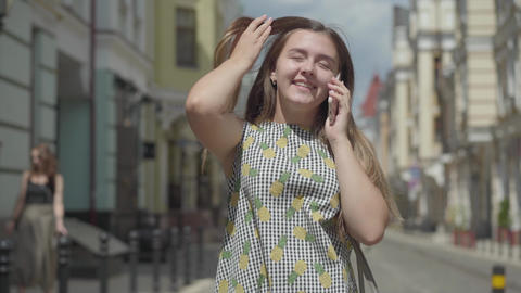 Cute young woman walking around the old european city, talking on the phone Footage