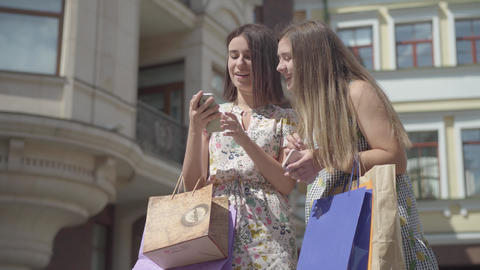 Two cute girlfriends after shopping with shopping bags taking selfie on Footage