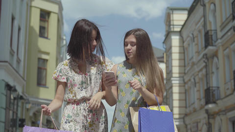 Two happy girlfriends after shopping with shopping bags in front of beautiful Footage