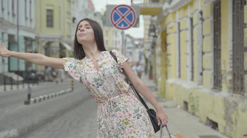Carefree young woman wearing summer dress with shopping bags in hands trying to Footage