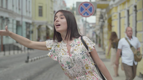 Pretty carefree young woman wearing summer dress with shopping bags in hands Footage
