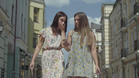 Two adorable girlfriends after shopping with shopping bags in front of beautiful Footage