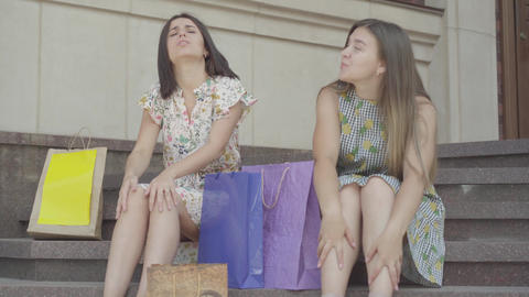 Two attractive girlfriends sitting on the stairs after shopping with shopping Footage