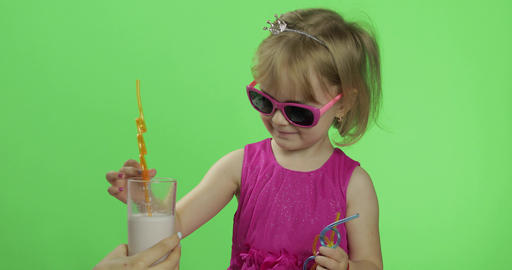 Happy four years old child in pink dress drinks milkshake cocktail. Chroma Key Live Action