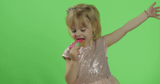 Girl in glossy dress begins to eat cookies in the form of strawberries Live Action