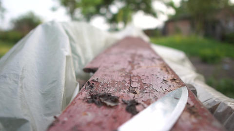 Kitchen knife lying on an old wooden board in a yard in summer in slow motion Footage