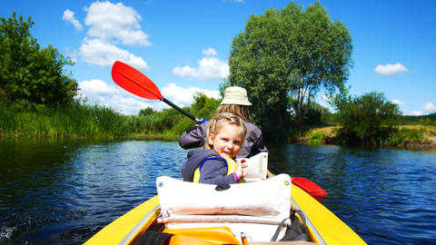 A child in a kayak on the river. Family outdoor activities Live Action