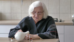 Old woman is pouring alcohol (mead) into a glass Footage